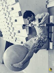 Escalador entrenando en la barra de dominadas con pelota fitball