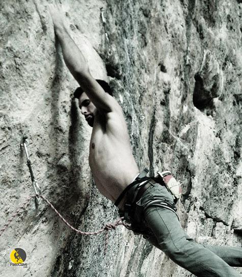 un escalador luchando con el core para soportar la puerta en una via de escalada deportiva en libre