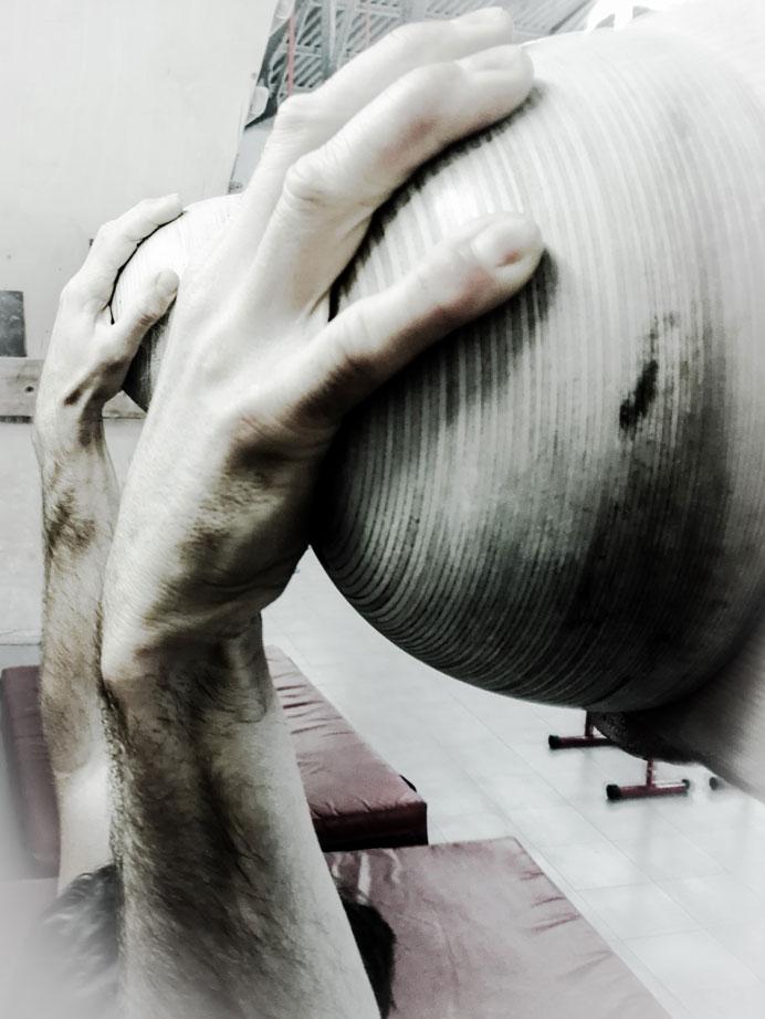 escalador entrenando fuerza de dedos con suspensiones sobre romos