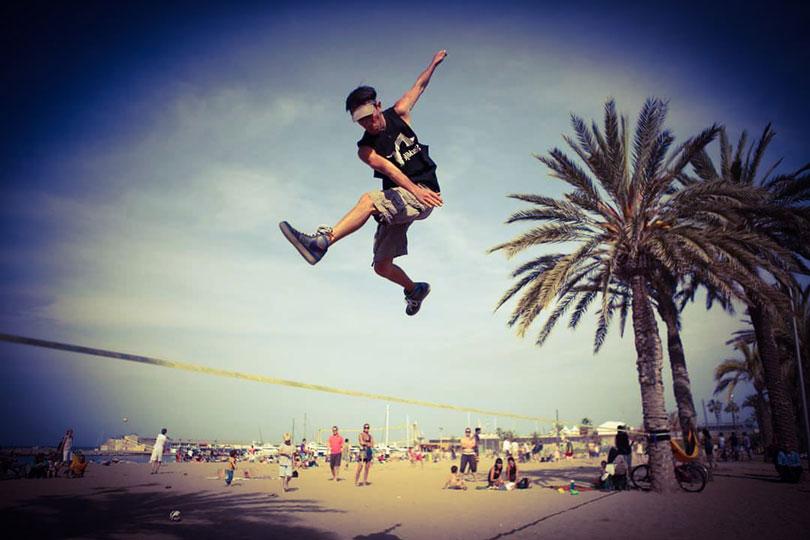 un Slackliner practicando trickline en la playa de barcelona