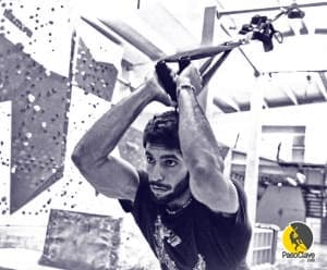 un escalador realizando extensiones de triceps con un sistema de suspensión de cintas trx en un rocódromo