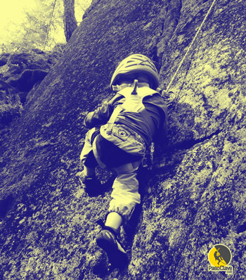 niño escalando con un arnés de cuerpo completo