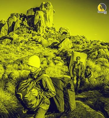 escaladores andando muy cargados con mochilas