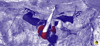 escalador reposando cambiando bidedos en una vía de escalada deportiva en roca