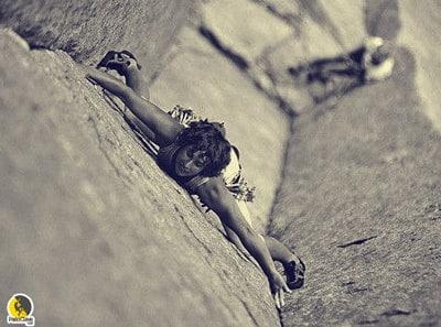 escaladora entrenando la flexibilidad de la cadera mientras escala un diedro