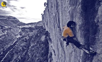 escalador en una vía de escalada deportiva con Chulilla al fondo
