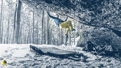 escalador escalando boulder con nieve y frío
