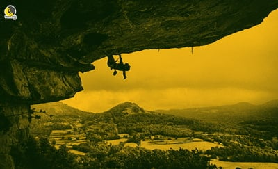 Escalador agitando los brazos mientras reposa escalando