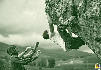 Escalador de boulder escalando mientras sus compañeros portean