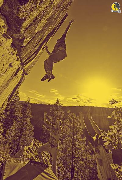 escalador de búlder haciendo un lance o movimiento dinámico mientras sus compañeros portean