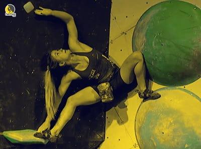 Escaladora escalando romos y volúmenes en una competición de boulder